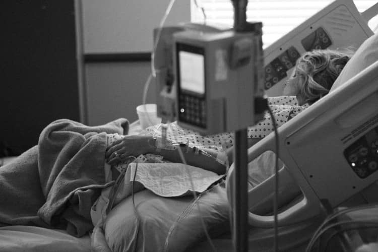 Black and white image of woman in a hospital bed, in need of a legal guardian.