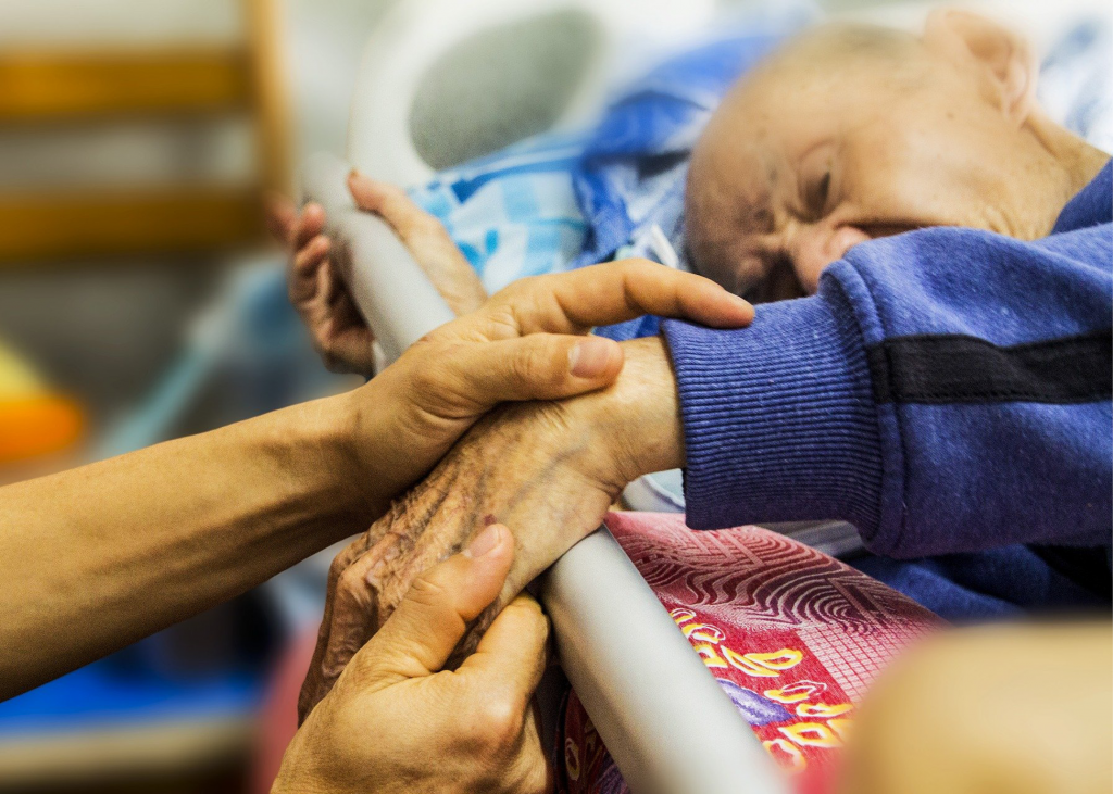 An elderly man laying in a hospice bed. Two younger hands are holding his.