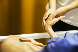 Guardianship of the Person and Property case. Close up shot of a young woman's hands clasped around the left hand of her elderly relative laying in a hospital bed.