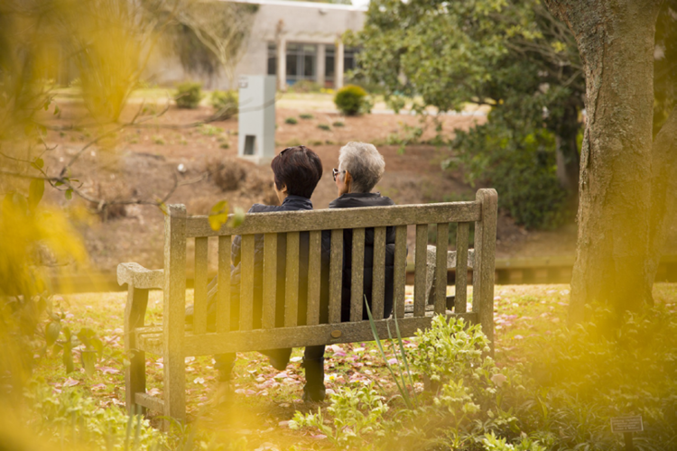 Image on Guardianship of the Property page. A woman and her elderly mother sitting on a park bench with trees and flowers all around.