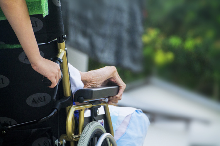 Temporary guardianship case. Closeup image of a young woman's arm pushing the wheelchair of her elderly relative.