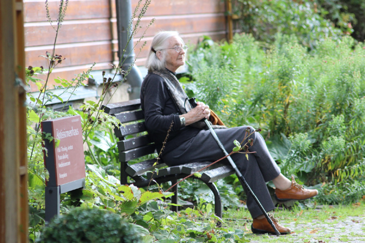 How Do I Protect My Elderly Parents at Home Blog Image: An elderly lady holding a cane is sitting on a bench surrounded by green bushes.