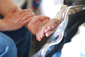 How to Deal with Elderly Parents Blog Image: An adult child holding the hand of his sick mother.