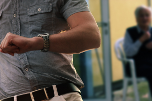 Elder Neglect Attorney Blog Image: In the foreground, a closeup of a young man in a button up looking at his watch. He is walking away from an elderly man blurred in the background.