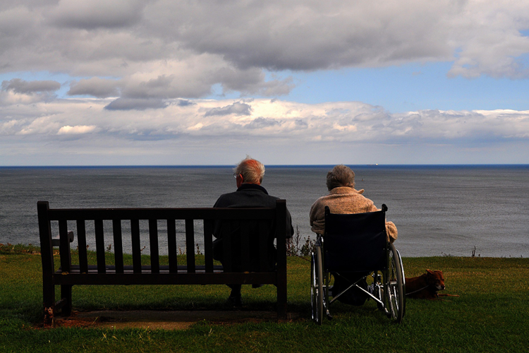 Long Term Care Planning Blog Image: A elderly man sitting on a wooden park bench overlooking the ocean. An elderly woman in a wheelchair sitting by his side.